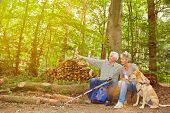 Senior couple with dog seeing goal of hiking trip in a forest