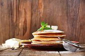 Stack of pancakes with mint and butter on rustic wooden background