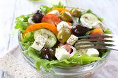 Greek salad in glass dish on napkin and color wooden background