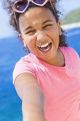 Selfie photograph of laughing happy mixed race African American female girl child wearing sunglasses in bright sunshine on vacation in front of a blue tropical sea