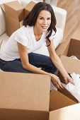 A beautiful single young woman packing or unpacking boxes and moving into a new house or home