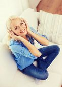 technology, music and happiness concept - smiling young girl sitting on sofa in headphones at home