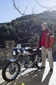 Man Standing Beside A Motorbike.