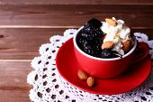 Dessert with prunes and almonds in red cup on lace doily and wooden planks background