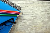 Notebook, eyeglasses and colorful pencils