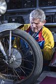 mechanic sanding the motorcycle wheel spokes