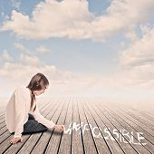 pic of impossible  - young girl turning the word impossible to possible with chalk - JPG