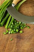 fresh green chives on wooden board with a special knife