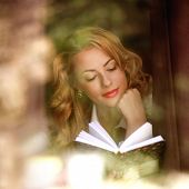 Beautiful Girl Reading A Book Indoors, The View Through Window With Reflections