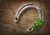 stock photo of horseshoe  - Old rusty horseshoe and four leaf clover on a wooden background - JPG