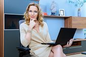 Beautiful business woman sitting on a couch and working on a laptop.