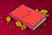Two Red Hearts Lying On The Book With Roses And Coffee Beans