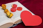 Three Red Candles Lying On The Book With Paper Heart