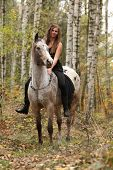 picture of appaloosa  - Young girl with appaloosa horse in autumn forest