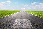 Mail, message symbol on long straight road, highway. Conceptual - post, shipping, parcel, e-mail,