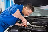 Mechanic using screwdriver on engine at the repair garage