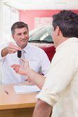 Smiling salesman giving a customer car keys at new car showroom