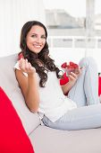 Pretty brunette eating strawberries on couch at home in the living room