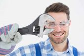 Portrait of confident repairman wearing protective glasses while holding wrench on white background