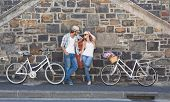 Attractive couple standing with bikes on a sunny day in the city
