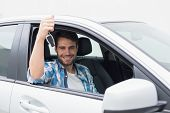 Young man smiling and holding key in his car
