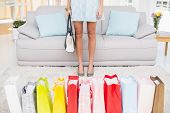 Stylish woman with shopping bags at home in the living room