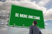The word be more awesome and businessman standing with hand on hip against sky