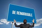 The word be remarkable and gesturing businessman against cloudy sky with sunshine