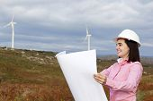 Female engineer holding a blueprint at wind turbine site