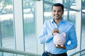 picture of money  - Closeup portrait happy smiling businessman placing money in pink piggy bank isolated indoors office background - JPG