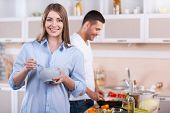 stock photo of heterosexual couple  - Happy couple cooking together in the kitchen while woman looking at camera and smiling - JPG