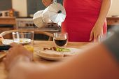 pic of coffee crop  - Cropped shot of woman serving black coffee in small glass on breakfast table - JPG