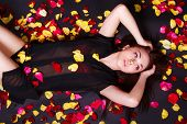 foto of black woman spa  - Beautiful young woman laying on sparse rose petals over black background - JPG