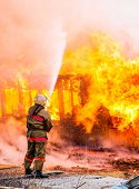 picture of fire extinguishers  - Fireman extinguishes a fire in an old wooden house - JPG
