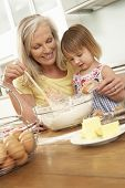 stock photo of grandmother  - Young Girl Helping Grandmother To Bake Cakes In Kitchen - JPG