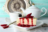 foto of cheesecake  - Tasty piece of cheesecake with berry sauce on plate on table close up - JPG