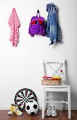 image of baseboard  - Children things hanging on wall and stacked in room - JPG