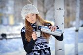 stock photo of thermos  - beautiful girl with thermos and cup hot tea in frosty winter day - JPG