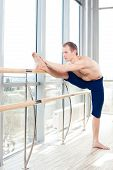 image of ballet barre  - in the hall man doing stretching near Barre - JPG