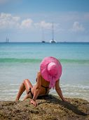 picture of beach hat  - Summer vacation woman on the beach in beach hat enjoying summer holidays looking at the ocean - JPG