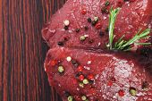 image of peppercorns  - fresh raw beef fillet mignon on old retro style wood as background with rosemary peppercorn and salt - JPG