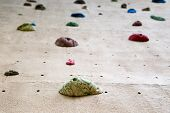 stock photo of climbing wall  - shallow depth of field looking up a climbing wall focused on the foot grip closest to the camera - JPG