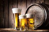image of beer mug  - Two glasses and mug of light beer on a background of the old wooden barrels - JPG