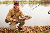stock photo of fisherman  - A young man with a fish in his hands and spinning - JPG
