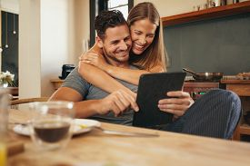 stock photo of socialism  - Couple smiling as they read a tablet computer together in morning in the kitchen. Young man and woman catching up on social media smiling. Woman hugging her boyfriend holding tablet PC.