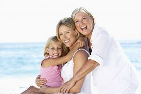 pic of grandmother  - Grandmother With Daughter And Granddaughter Embracing On Beach Holiday - JPG