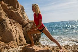 stock photo of tanga  - Sexy girl in sportswear and tanga string training on the cliff of the rocky beach - JPG