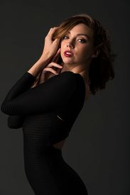 stock photo of tight dress  - Beautiful young brunette in a tight black dress - JPG