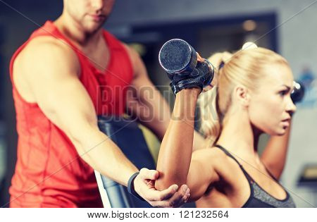 sport, fitness, bodybuilding, lifestyle and people concept - man and woman with dumbbells flexing mu