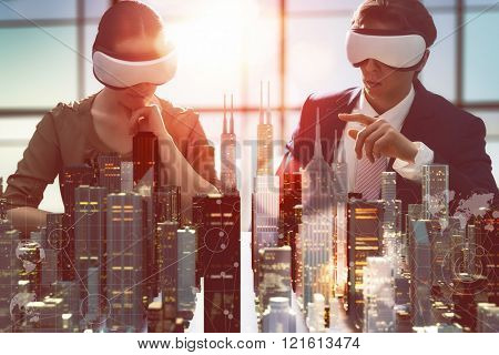 two business persons are developing a project using virtual reality goggles. the concept of technolo